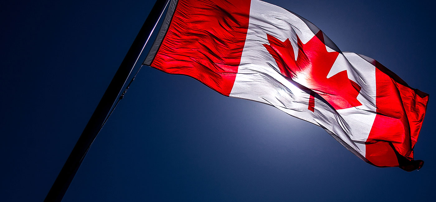 Canadian flag blows in the wind on a blue, sunny day