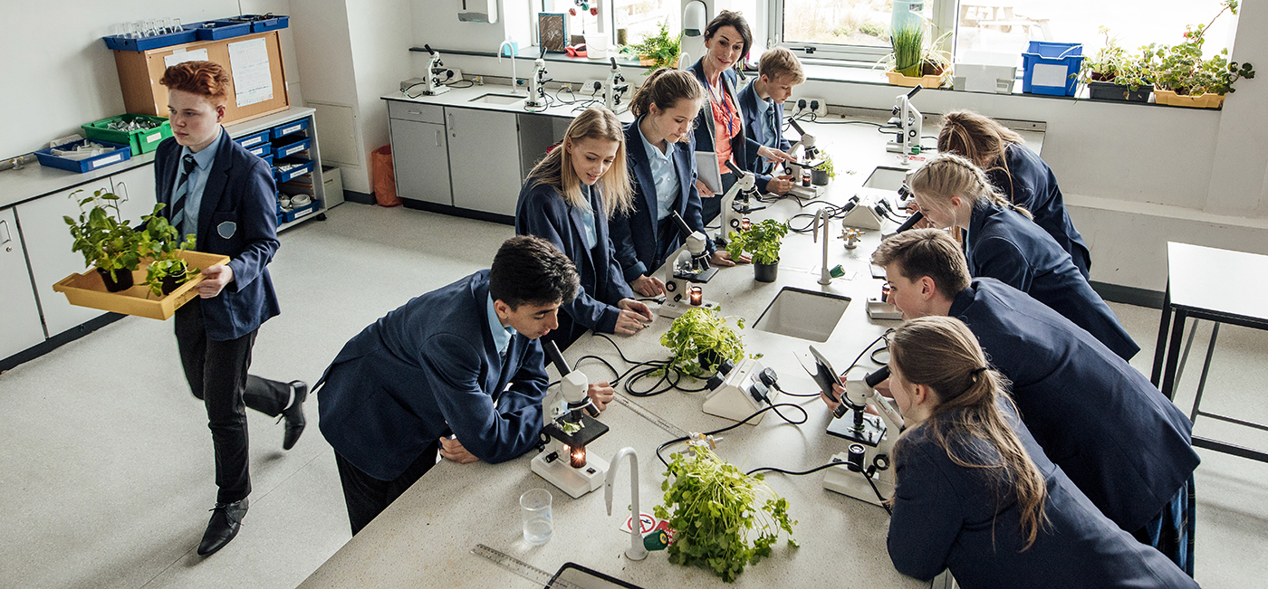 High school students in science class with teacher examining plants with microscopes