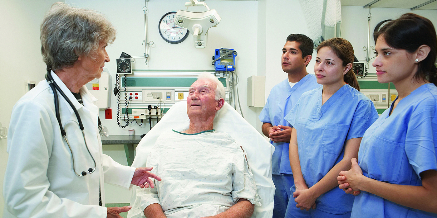 A physician discusses a patient's case with medical students, while patient sits up in a hospital bed.